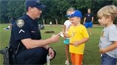 Officer giving stickers to kids