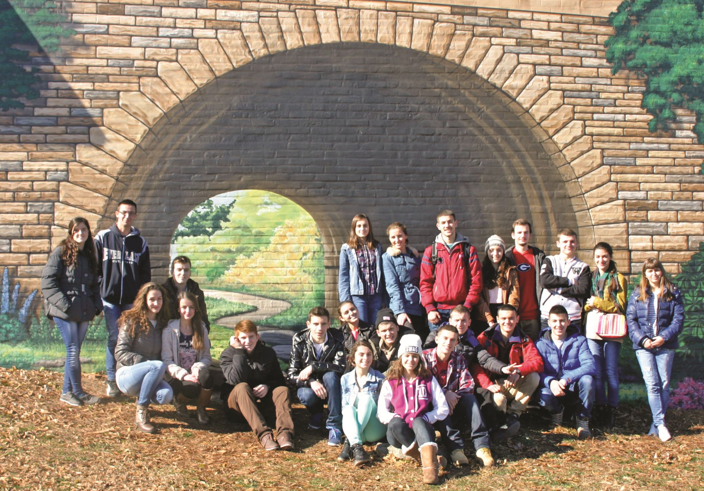 A student group poses at Lilburn Tunnel Bridge Mural on Railroad Avenue