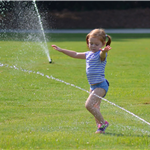 Girl in sprinkler